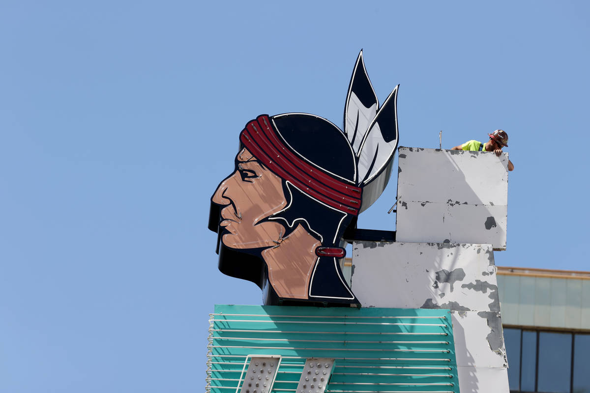 Workers install a new neon addition atop a sign at Hotel Apache at Binion's on Fremont Street a ...