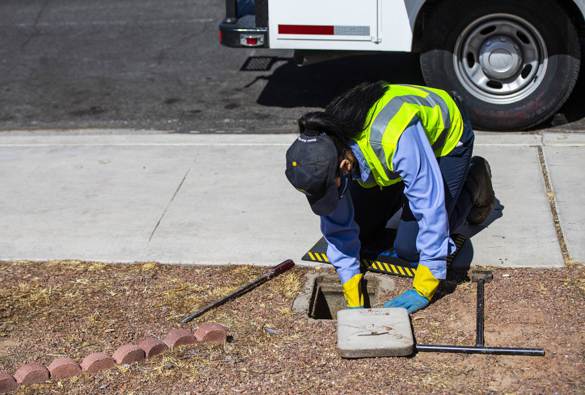 Letty Valenzuela, field technician at Las Vegas Valley Water District, checks on a water meter ...
