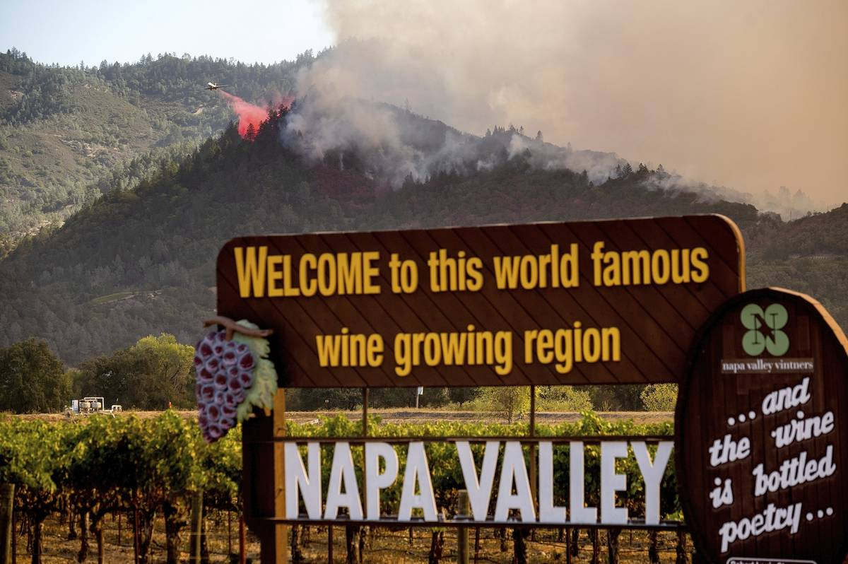 In this Sunday, Sept. 27, 2020, file photo, An air tanker drops retardant on the Glass Fire bur ...