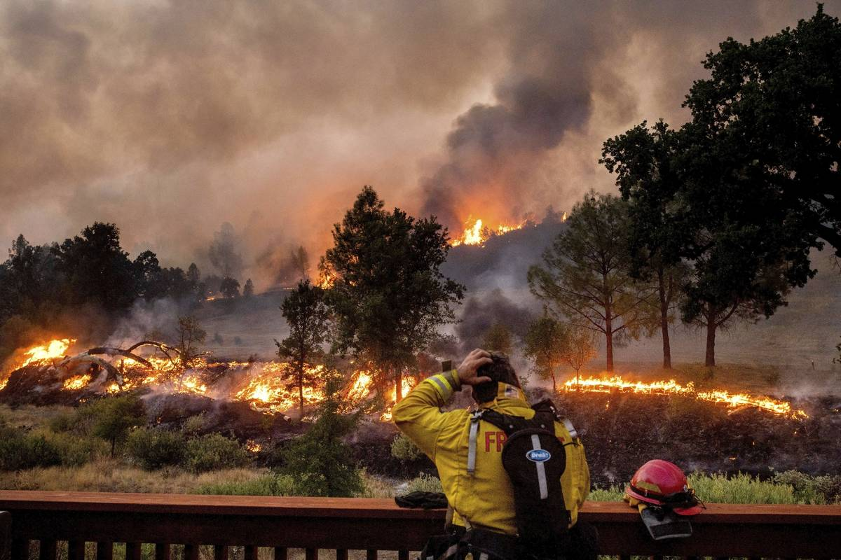 In this Aug. 21, 2020, file photo, a firefighter rubs his head while watching the LNU Lightning ...