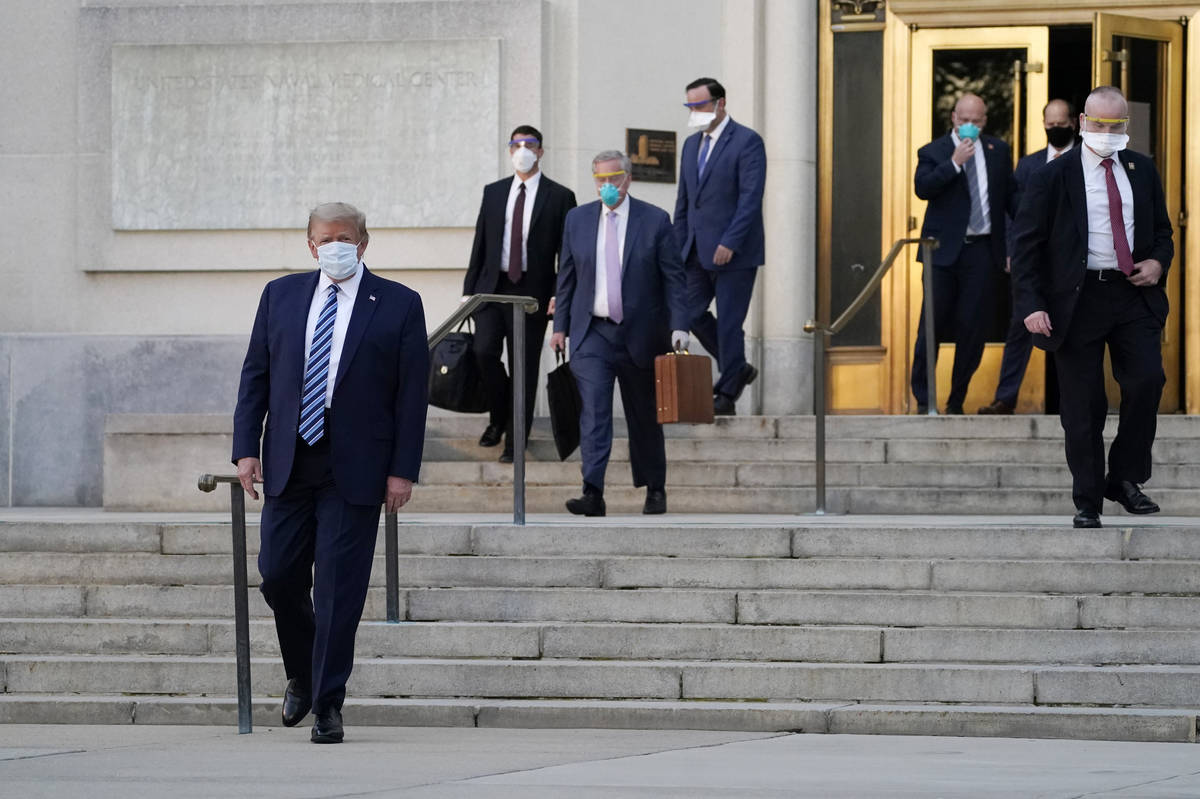 President Donald Trump walks out of Walter Reed National Military Medical Center to return to t ...