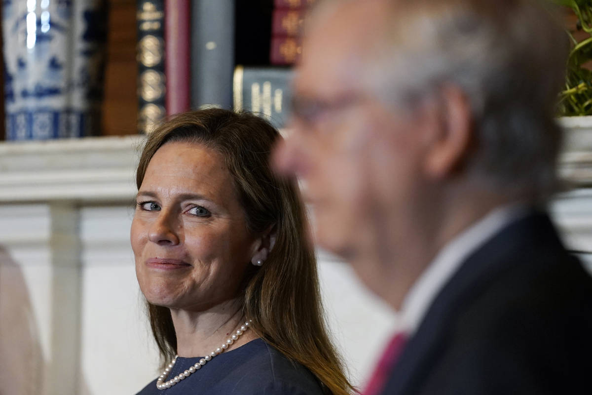 Supreme Court nominee Judge Amy Coney Barrett looks over to Senate Majority Leader Mitch McConn ...