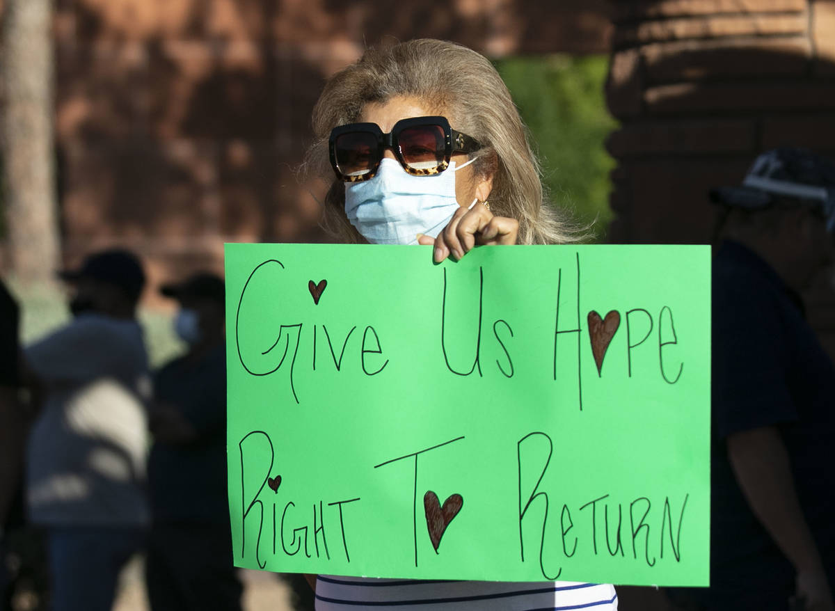 Reina Almuina, a waitress at Aria, holds a sign as she joins a rally outside of the Clark Count ...