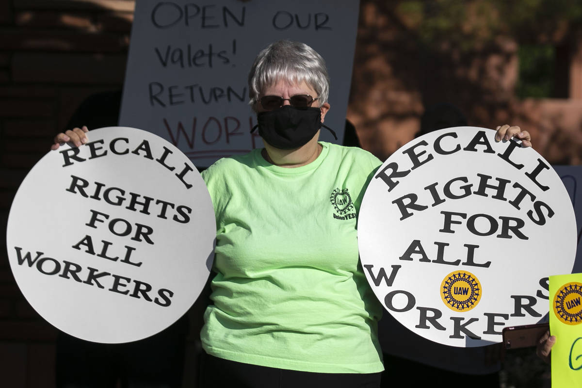Paula Schusster, a dealer at Flamingo, holds signs as she joins a rally outside of the Clark Co ...