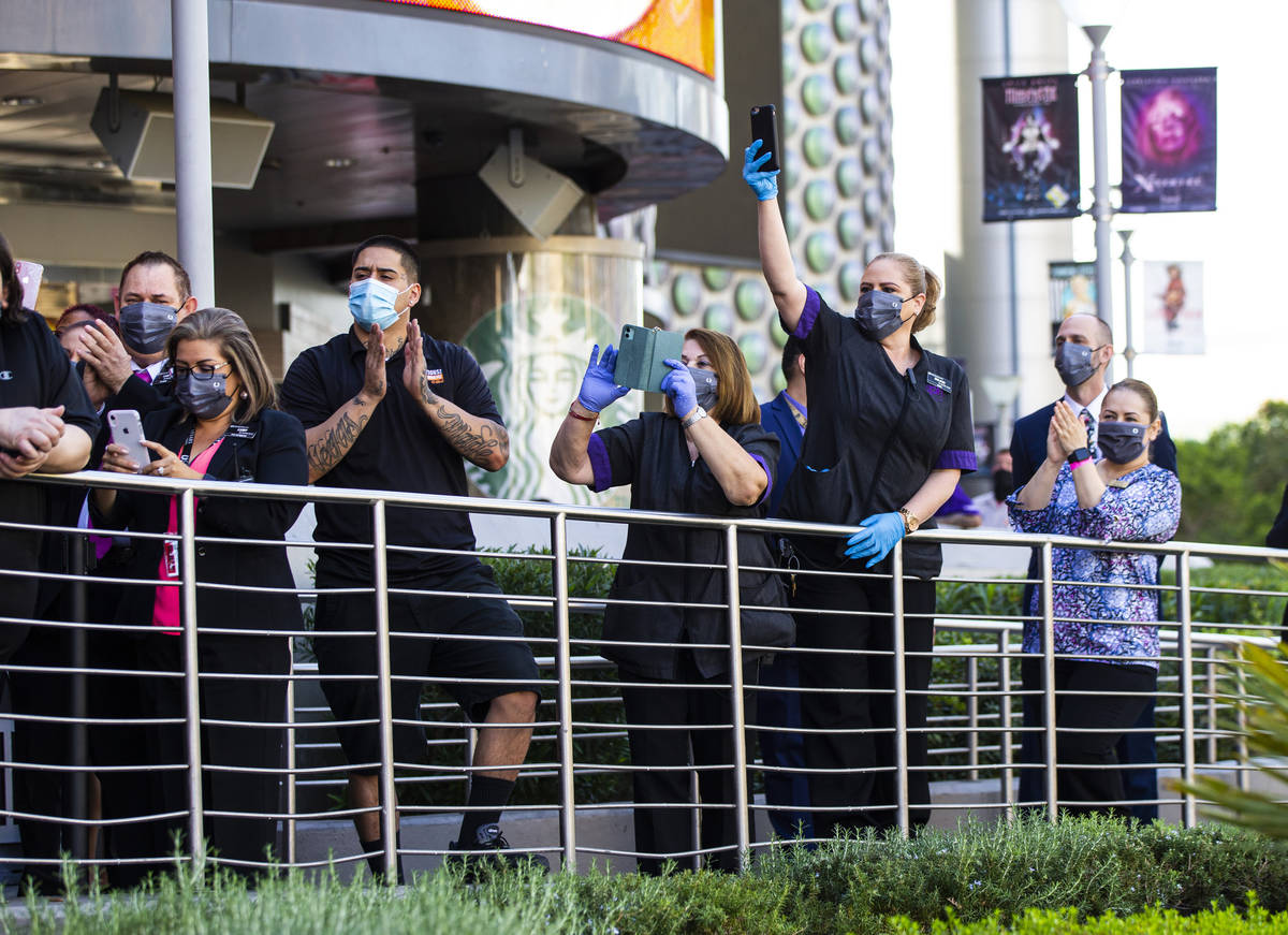 Employees watch as dancers perform to mark the reopening of the Planet Hollywood Resort in Las ...