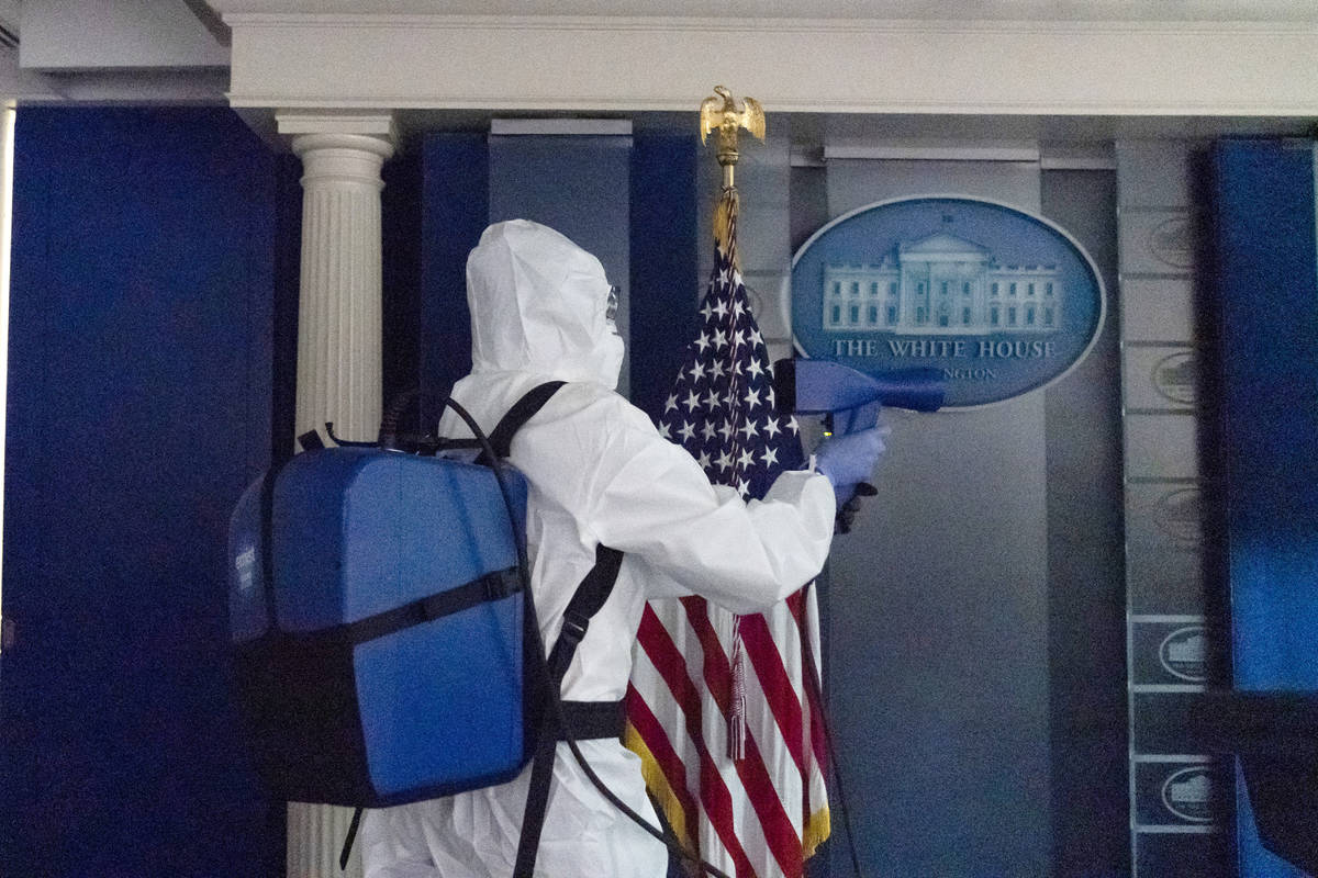 A member of the cleaning staff sprays The James Brady Briefing Room of the White House, Monday, ...
