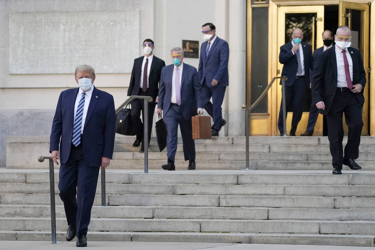 President Donald Trump, left, walks out of Walter Reed National Military Medical Center to retu ...