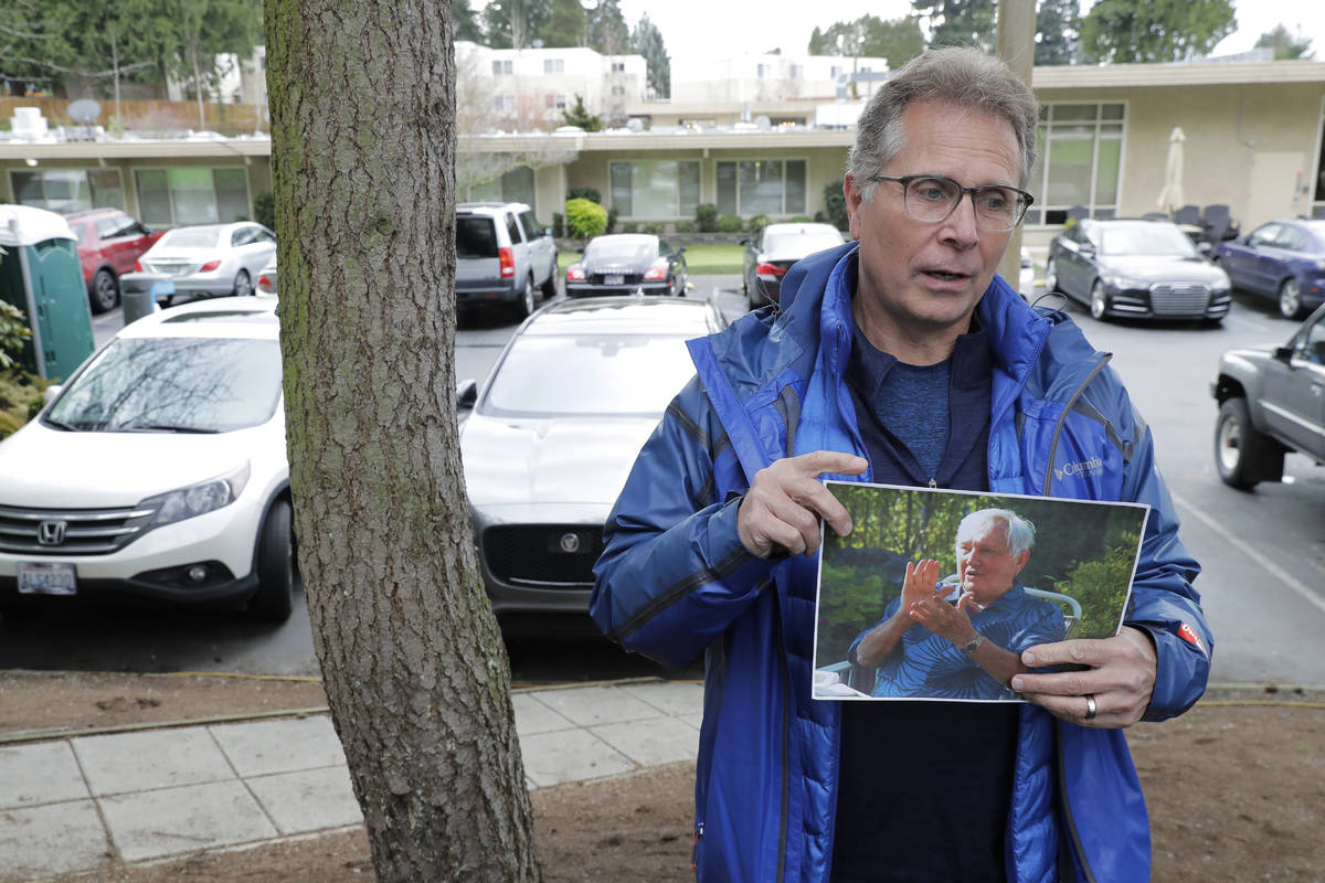 In this March 12, 2020, file photo, Scott Sedlacek poses while holding a photo of his father, C ...