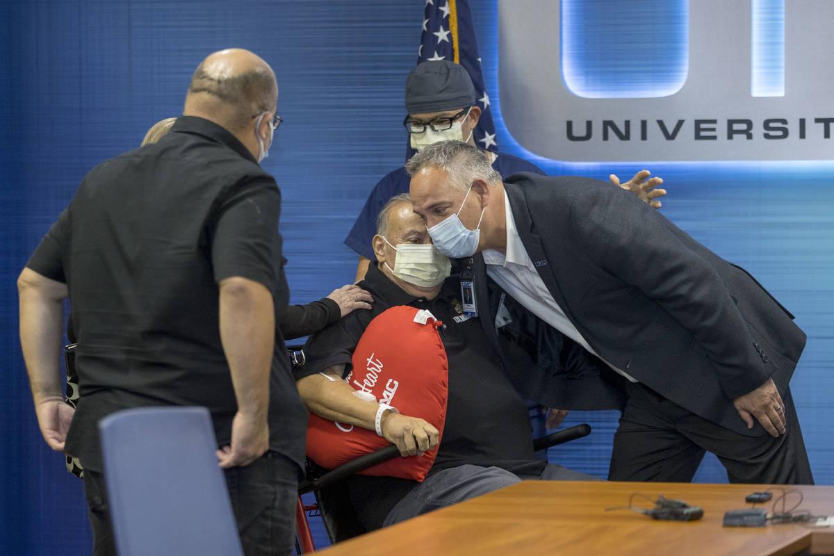 University Medical Center CEO Mason Van Houweling, right, hugs Pablo Bernabe, center, with chan ...