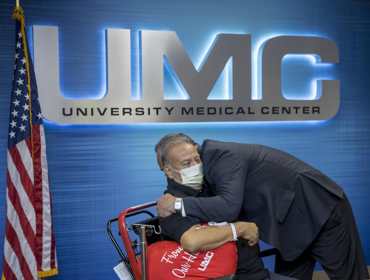 Pablo Bernabe, left, hugs University Medical Center CEO Mason Van Houweling, right, during a pr ...