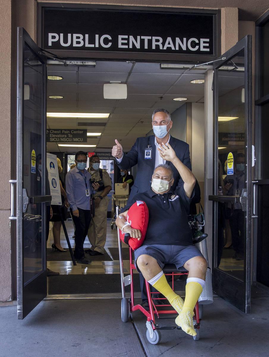University Medical Center CEO Mason Van Houweling, above, pushes Pablo Bernabe, center, as they ...