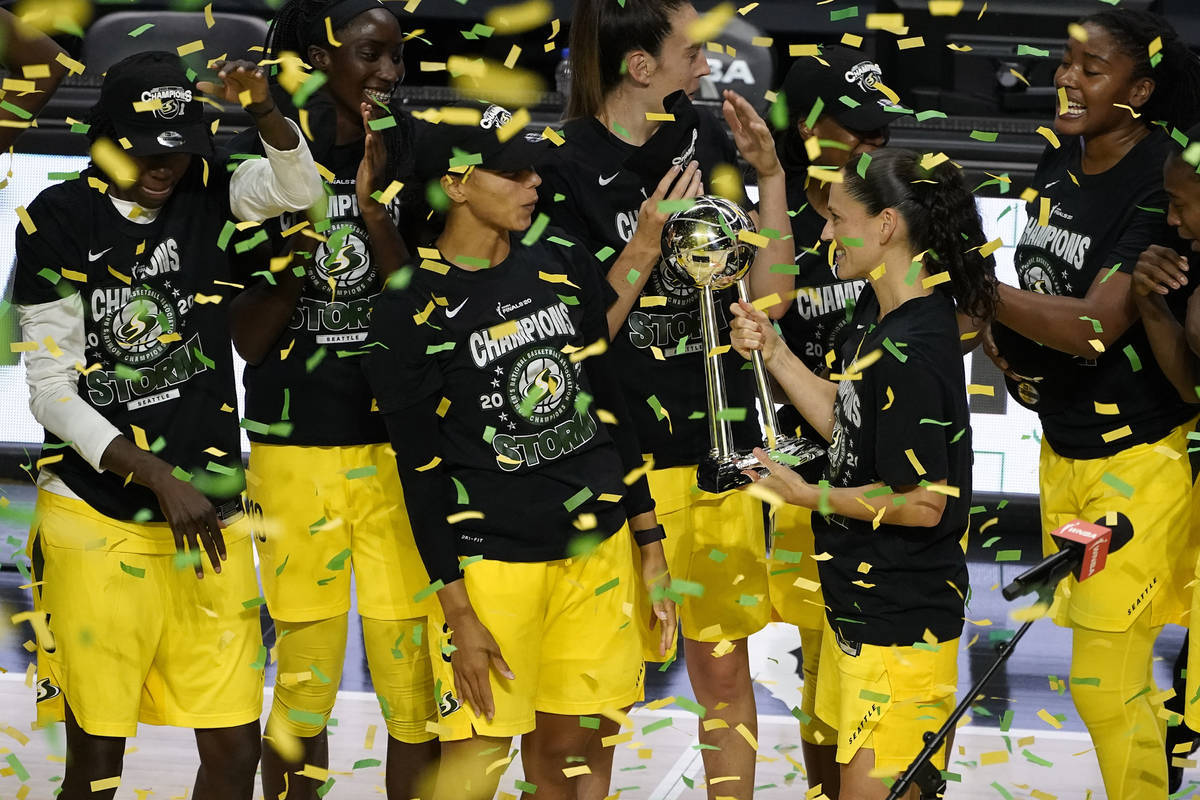 Seattle Storm guard Sue Bird shows the trophy to some of her teammates after the team defeated ...