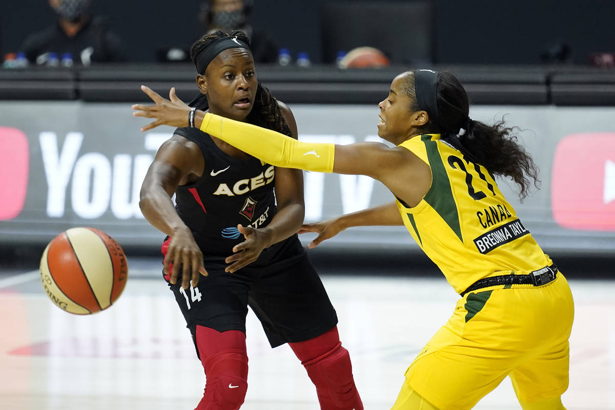 Seattle Storm guard Jordin Canada (21) knocks the ball away from Las Vegas Aces guard Sugar Rod ...