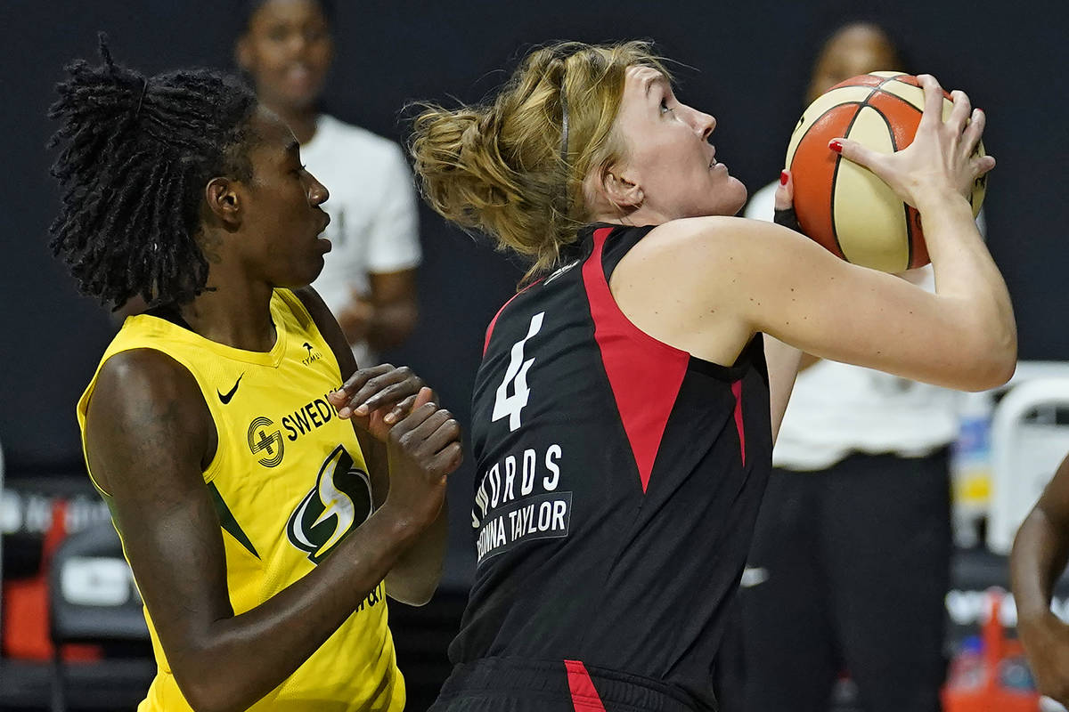 Las Vegas Aces center Carolyn Swords (4) shoots in front of Seattle Storm forward Natasha Howar ...
