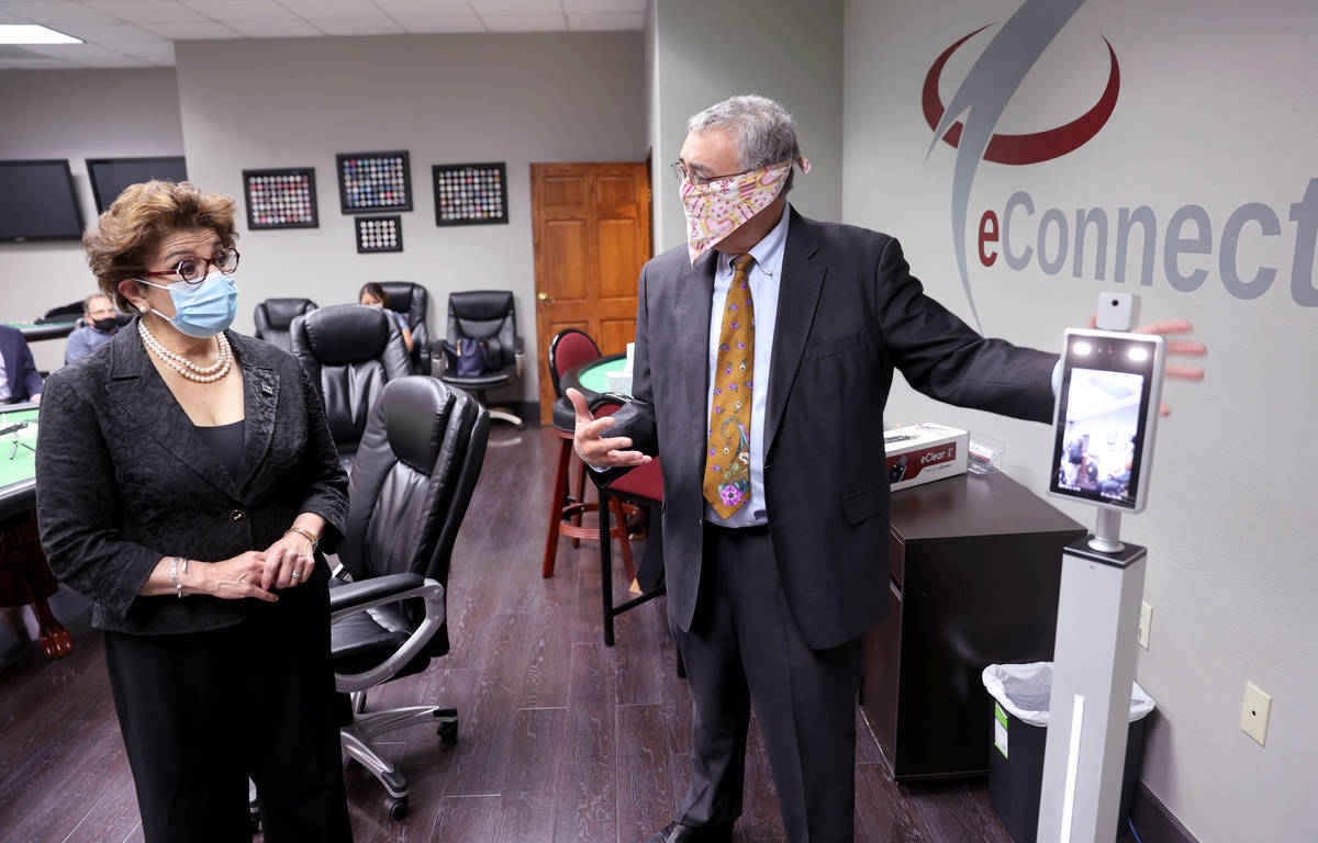 EConnect President and CEO Henry Valentino III, left, shows the eClear self-serve temperature c ...