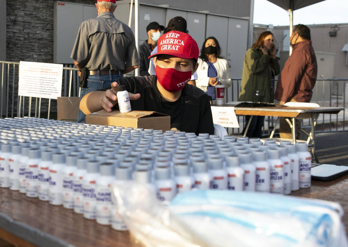 Make America Great Again event volunteer Gilbert Morales displays hand sanitizers at Boulder Ci ...