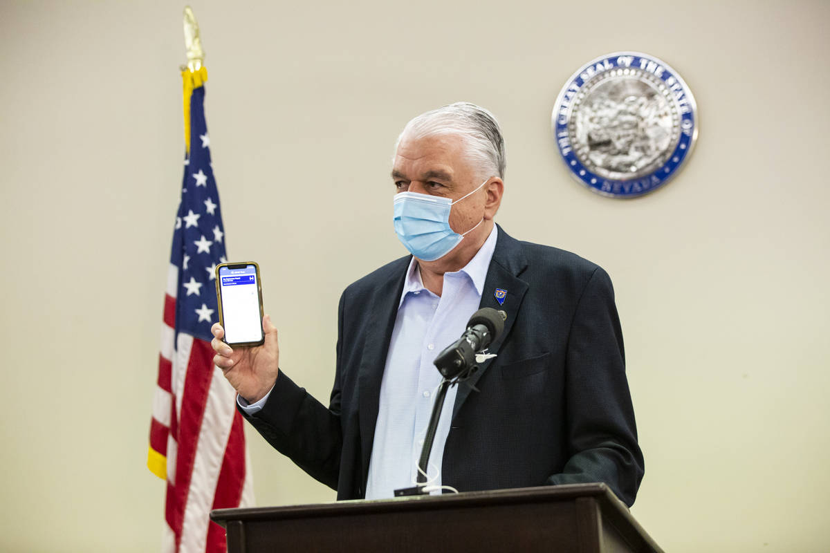 Gov. Steve Sisolak holds up a contact tracing app while giving an update on the state's COVID-1 ...