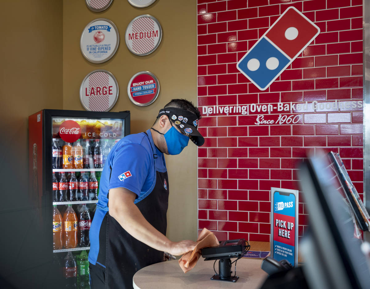 Domino's general manager Jessy Cortez sanitizes surfaces at the Domino's located off of East Wi ...