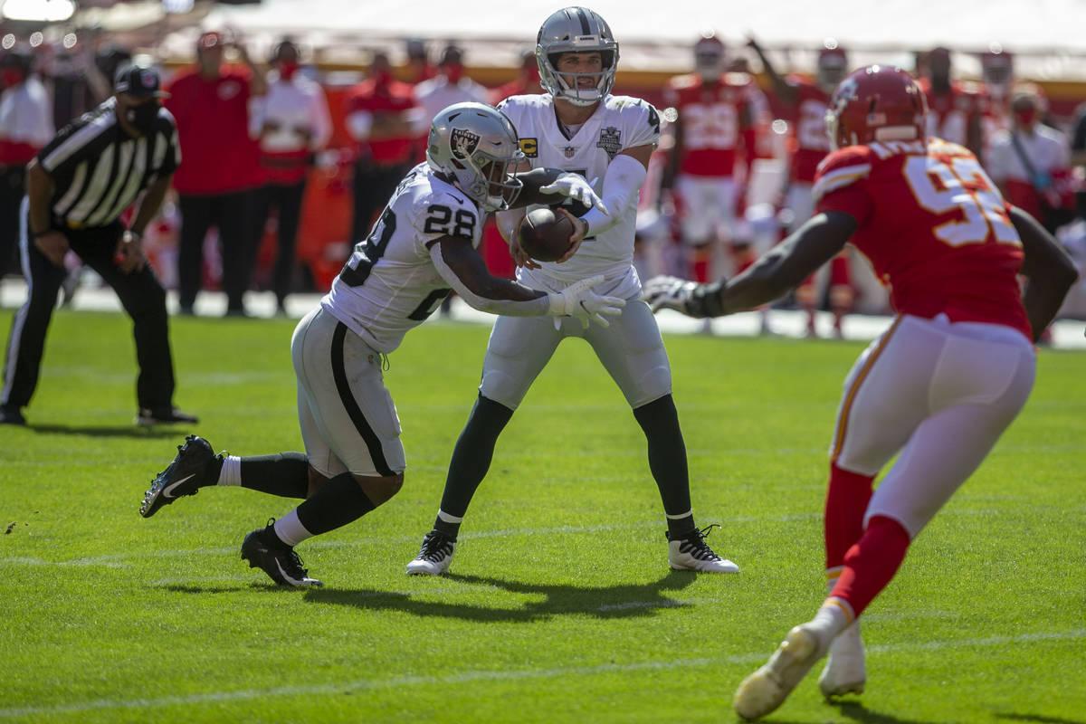 Las Vegas Raiders quarterback Derek Carr (4) hands off the football to running back Josh Jacobs ...
