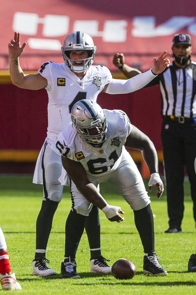 Las Vegas Raiders quarterback Derek Carr (4) calls a play at the line of scrimmage as center Ro ...