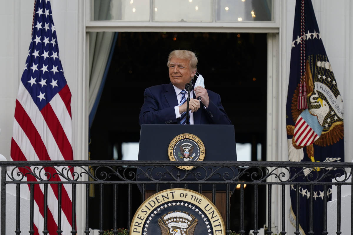 President Donald Trump removes his face mask to speak from the Blue Room Balcony of the White H ...