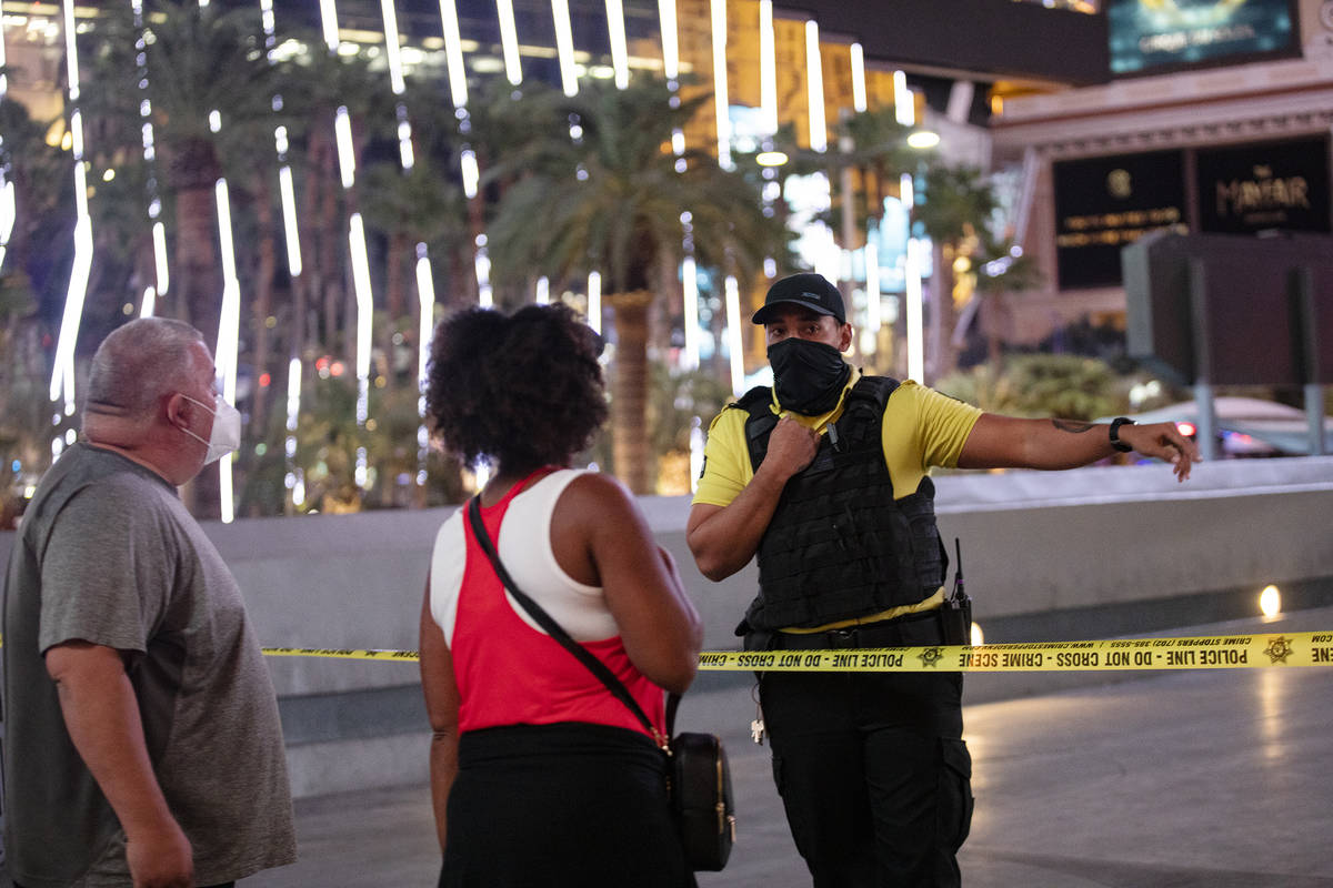 A security guard speaks with onlookers at the scene on the Strip where a man was shot at the Mi ...