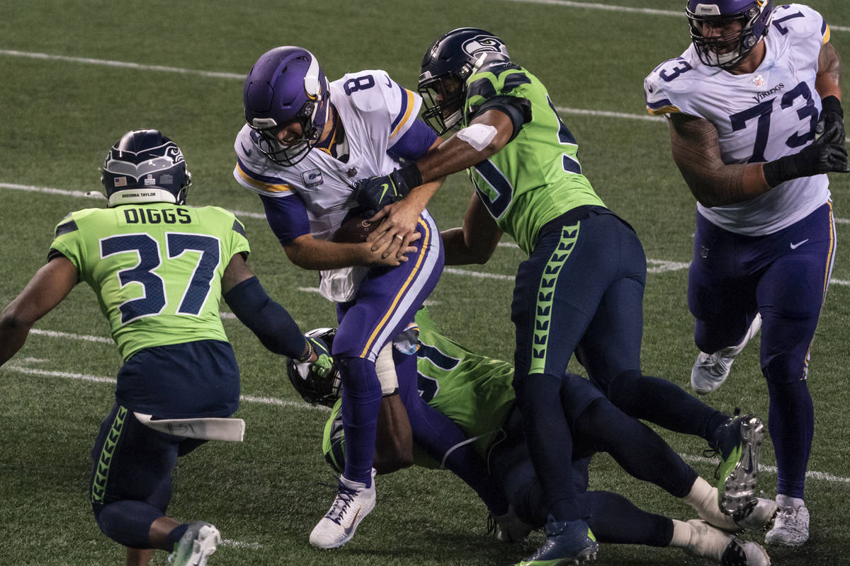 Minnesota Vikings quarterback Kirk Cousins is tackled by Seattle Seahawks defensive back Quandr ...