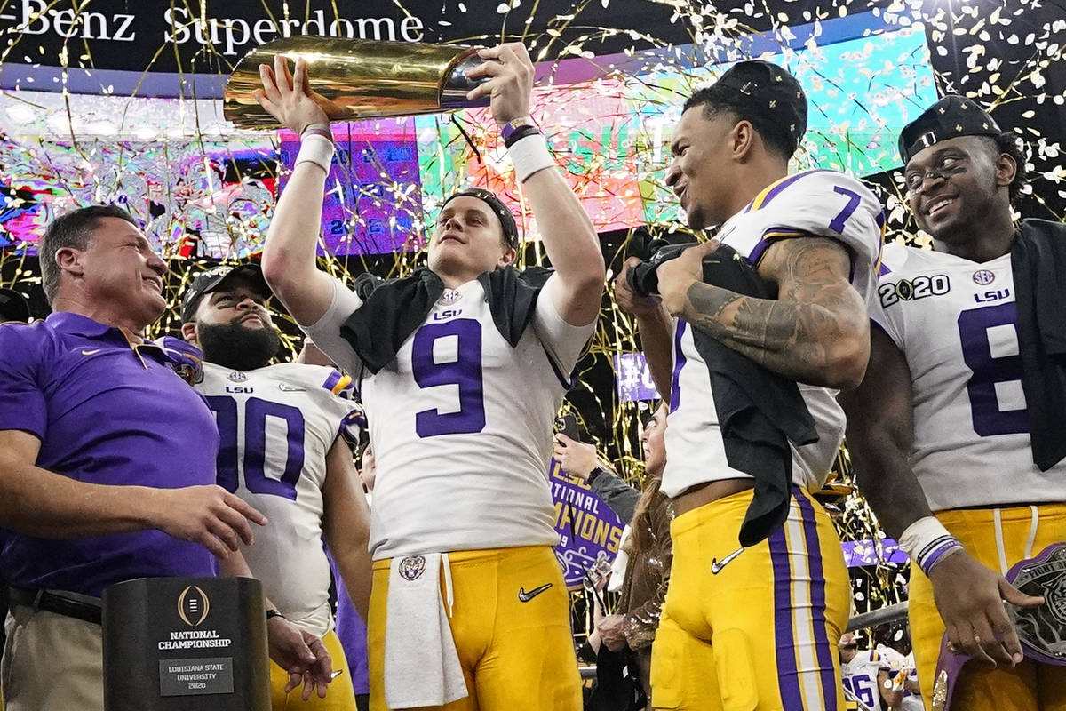 LSU quarterback Joe Burrow holds the trophy after their win against Clemson in a NCAA College F ...