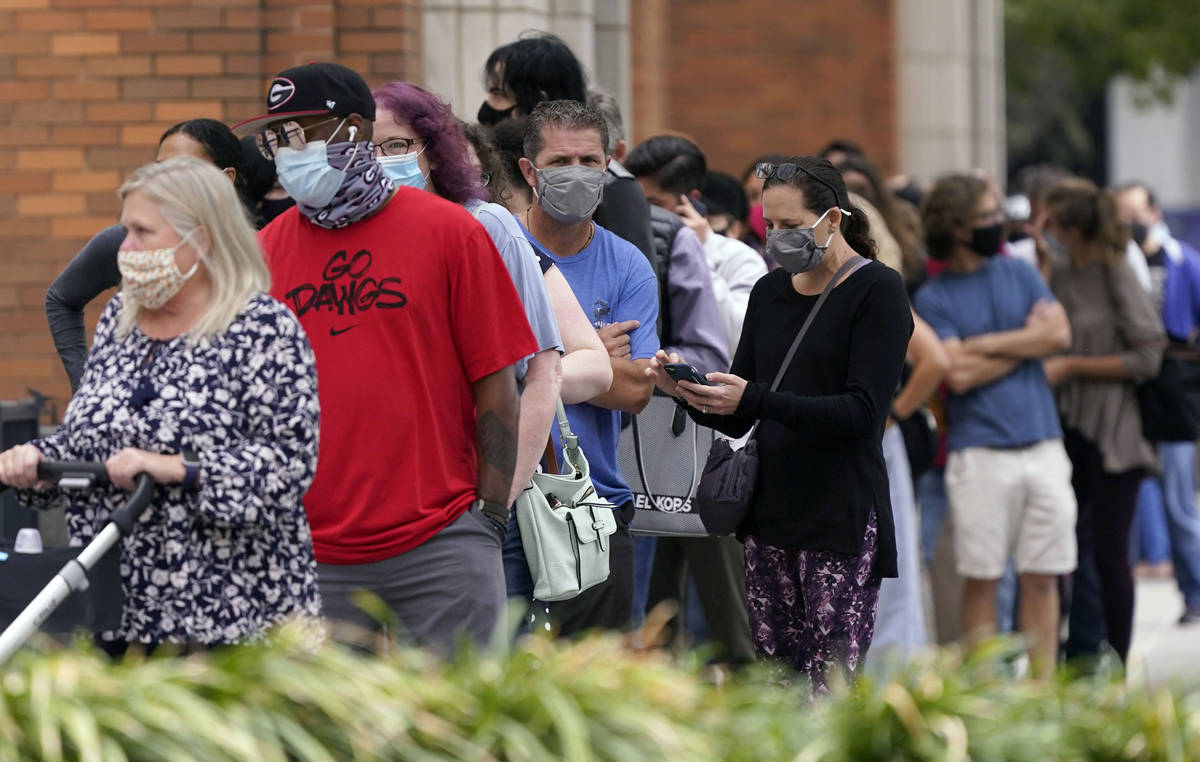 Voters line up and wit to cast a ballot at the American Airlines Center during early voting Thu ...