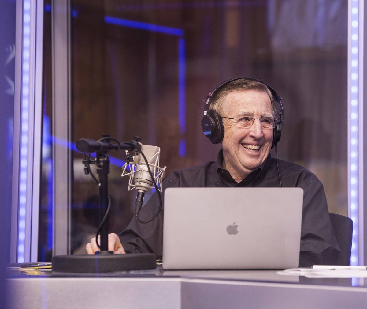 Brent Musburger shares a laugh with staff members during a live broadcast covering opening rou ...