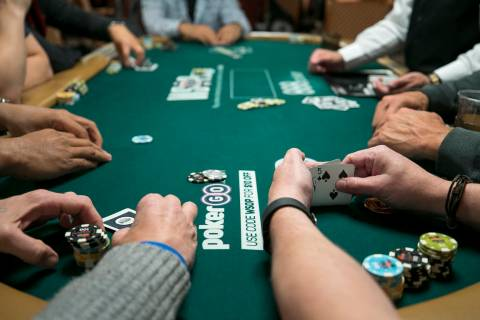 A poker player checks his cards during the World Series of Poker on Monday, June 26, 2017, at t ...
