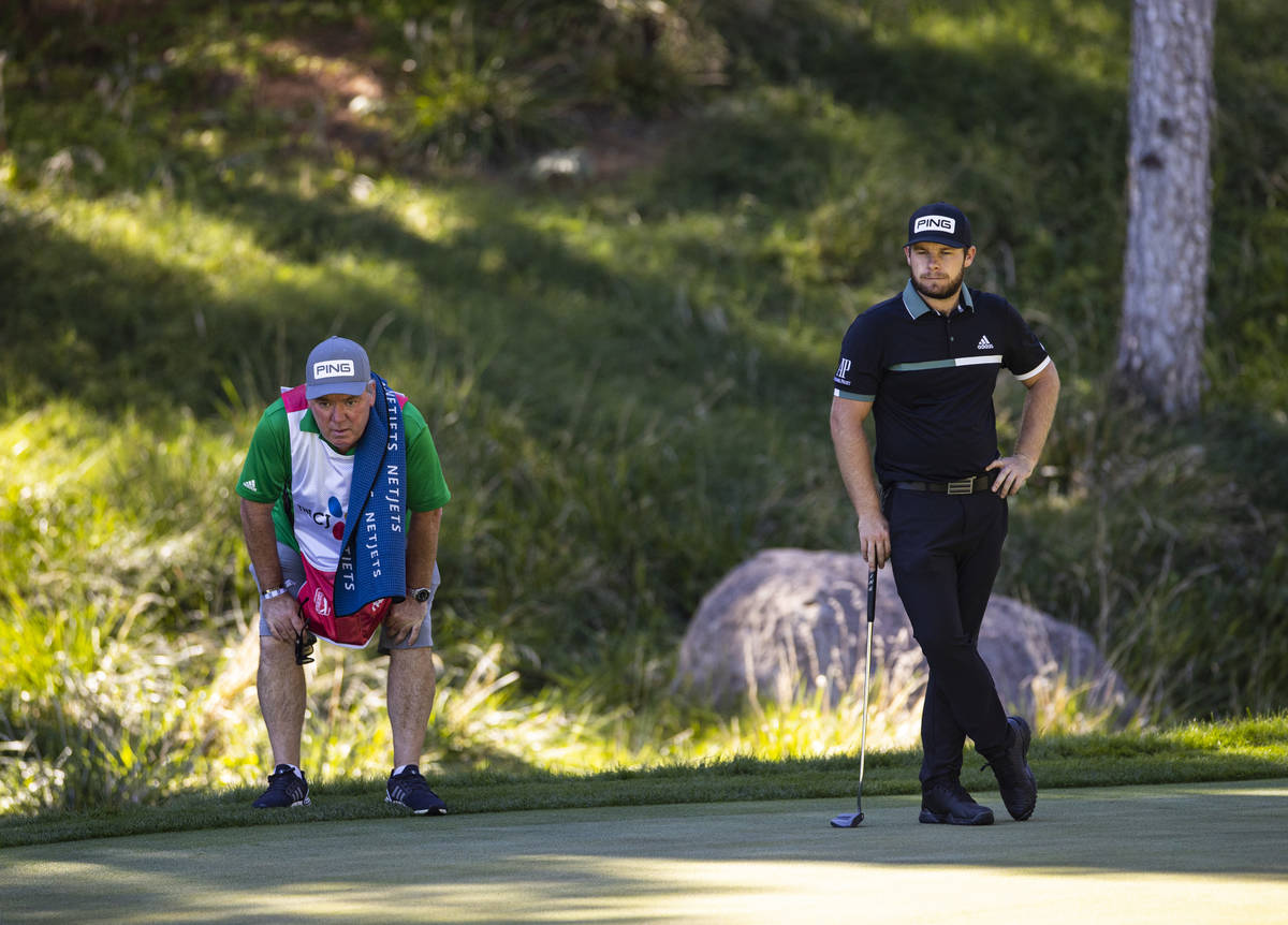 Tyrrell Hatton, right, keeps an eye on the ninth green with his caddie, Mick Donaghy, during th ...