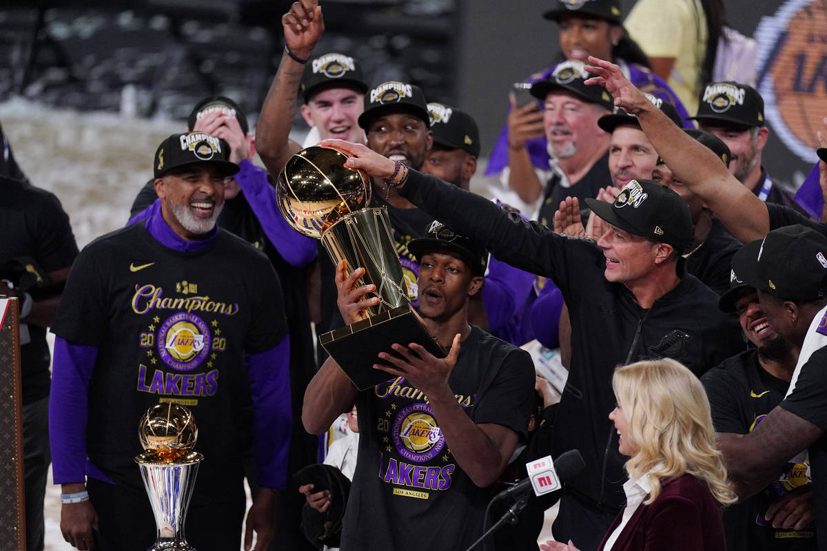 Los Angeles Lakers' Rajon Rondo (9) holds the trophy as he celebrates with his teammates after ...