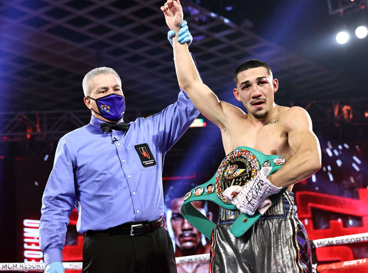 Teofimo Lopez has his arm raised in victory after his unanimous decision over Vasiliy Lomachenk ...