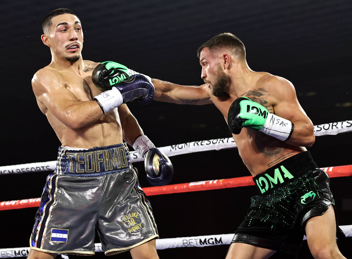 Vasiliy Lomachenko, right, lands a punch against Teofimo Lopez during their lightweight title f ...