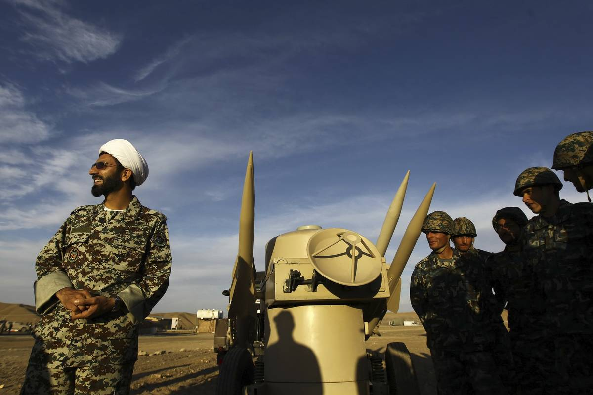 FILE - In this Nov. 13, 2012 file photo, an Iranian clergyman stands next to missiles and army ...