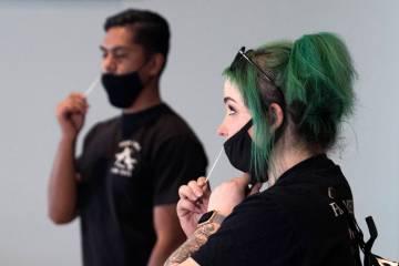 Nicole Thomas, right, a UNLV student volunteer, and Jake Inda, a volunteer, conduct self-swabbi ...
