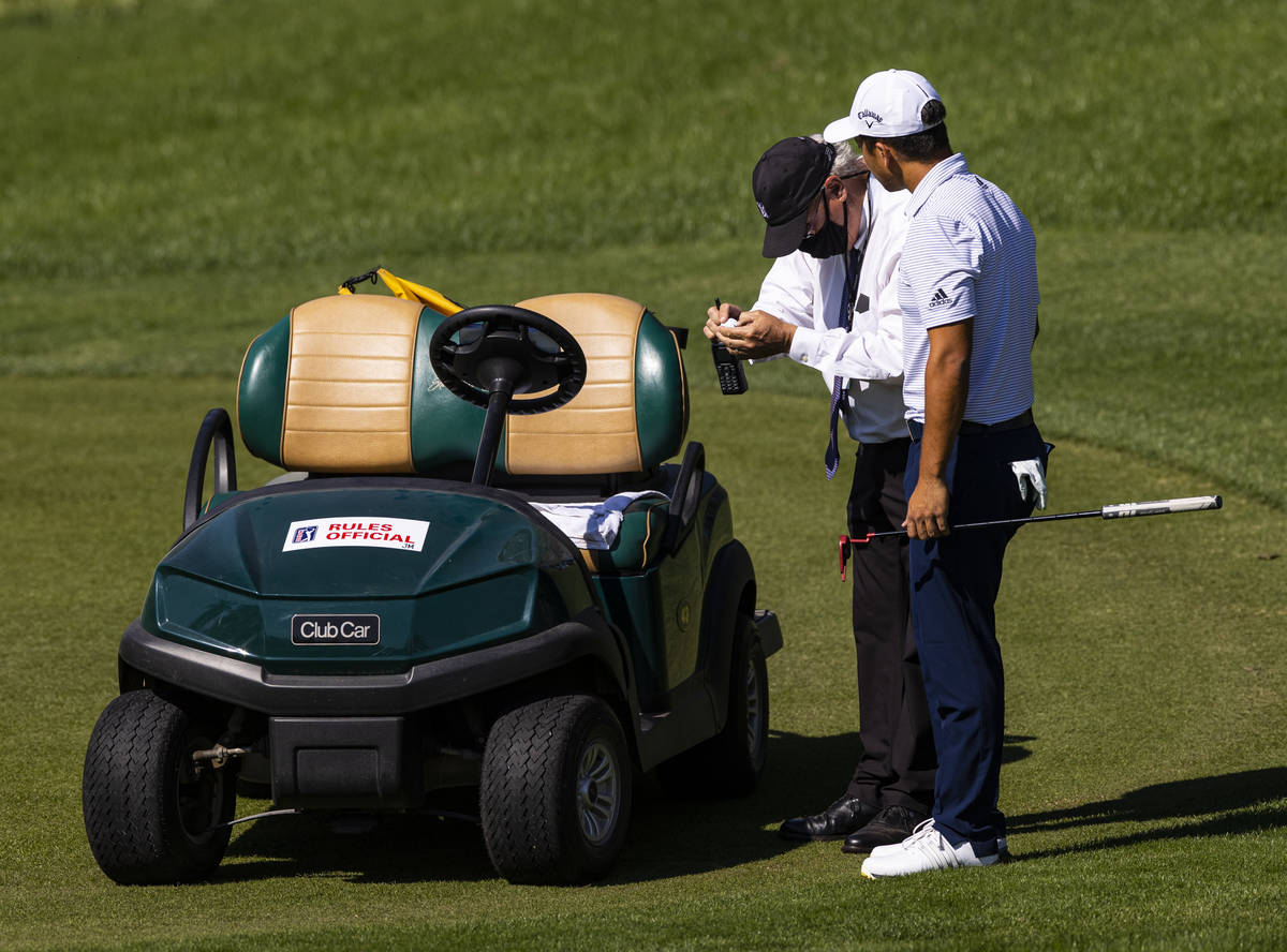 Xander Schauffele has a line official check a golf ball by seventh green during the final round ...