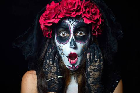 Portrait of woman dressed as catrina, skull to honor the dead in Mexico. Dressed with white fac ...