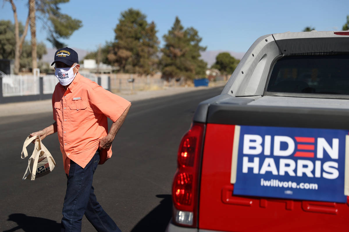 Canvasser Peter Ward of North Las Vegas walks from his car to drop off literature at the home o ...
