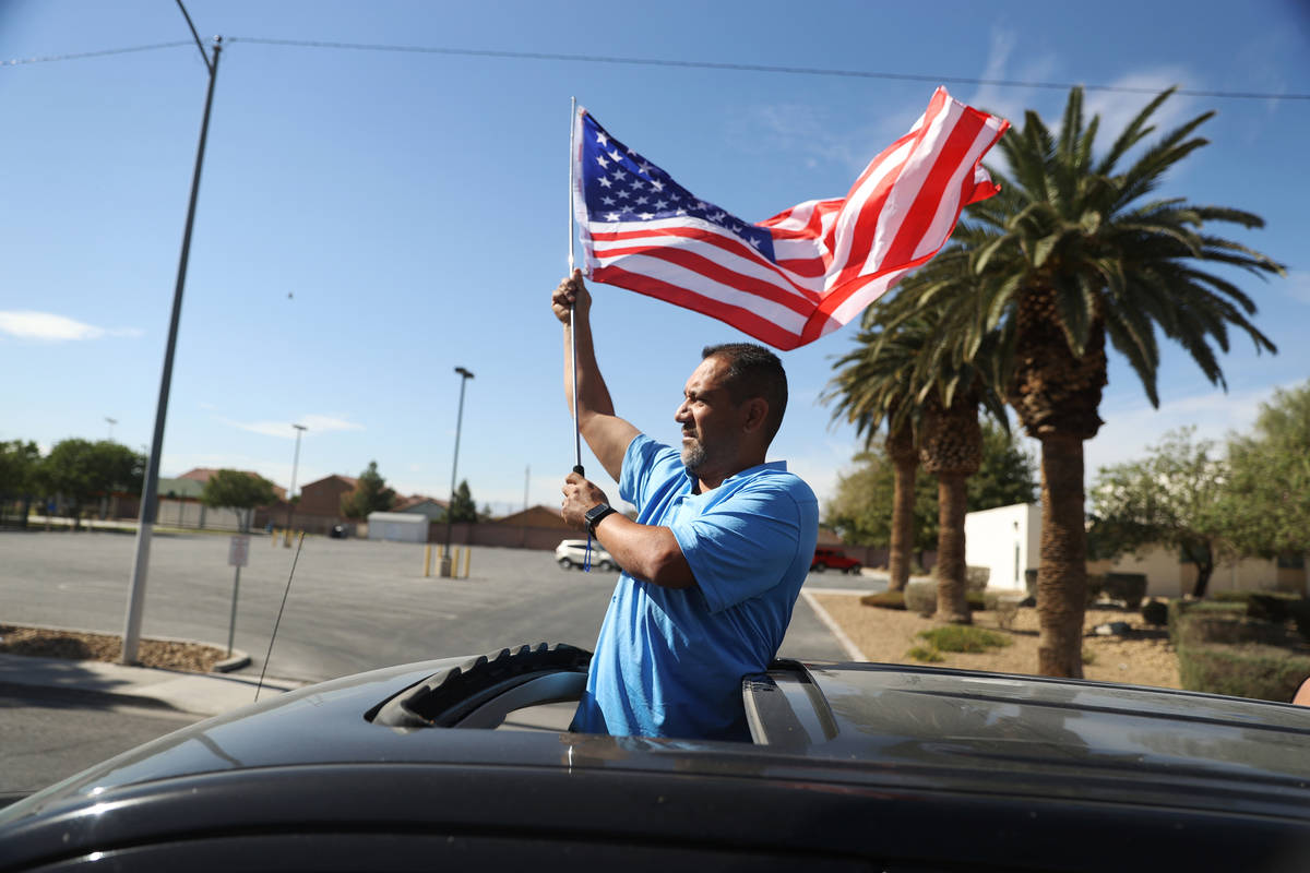Juan Prillwitz waves an American flag while participating during a campaign parade for Assembly ...