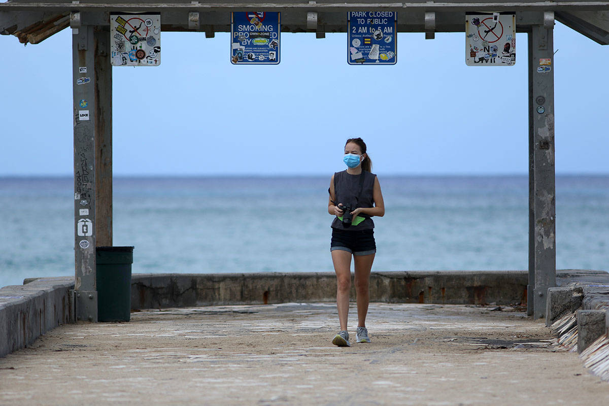A woman wears a mask as she walks along a closed Waikiki Beach pier in Honolulu on Saturday, Ma ...