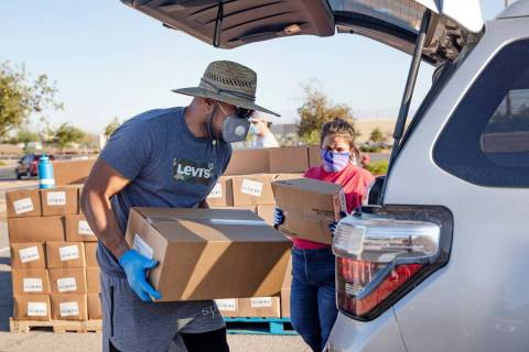 Volunteer Leonid Tuiasosopo, left, and Nicole McKinney, right, place food in the back of a pers ...