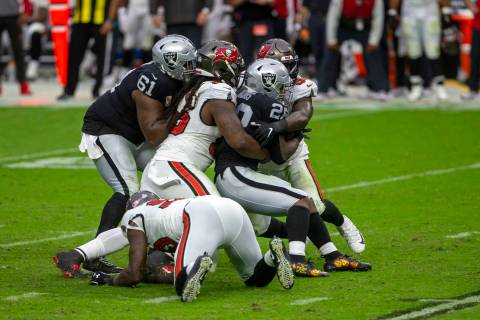 Las Vegas Raiders center Rodney Hudson (61) tries to assist as running back Josh Jacobs (28) is ...