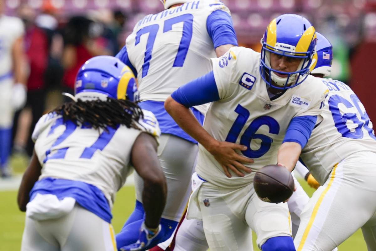 Los Angeles Rams' Jared Goff (16) hands off to Darrell Henderson (27) during the first half of ...
