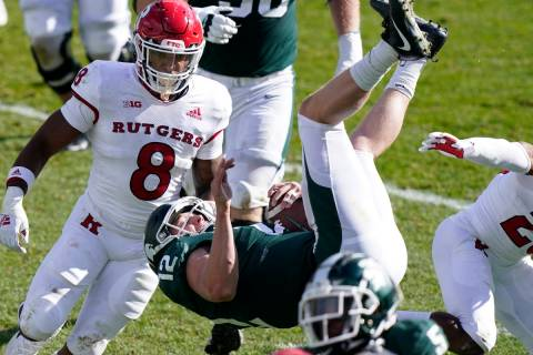 Michigan State quarterback Rocky Lombardi (12) jumps over Rutgers defensive back Lawrence Steve ...