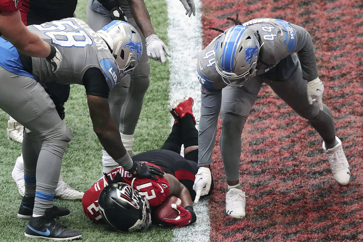 Detroit Lions players point at the football held by Atlanta Falcons' Todd Gurley during the fou ...