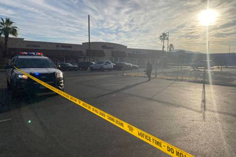 Crime scene tape stretches across a parking lot at Pecos-McLeod Plaza, 3050 E. Desert Inn Road, ...