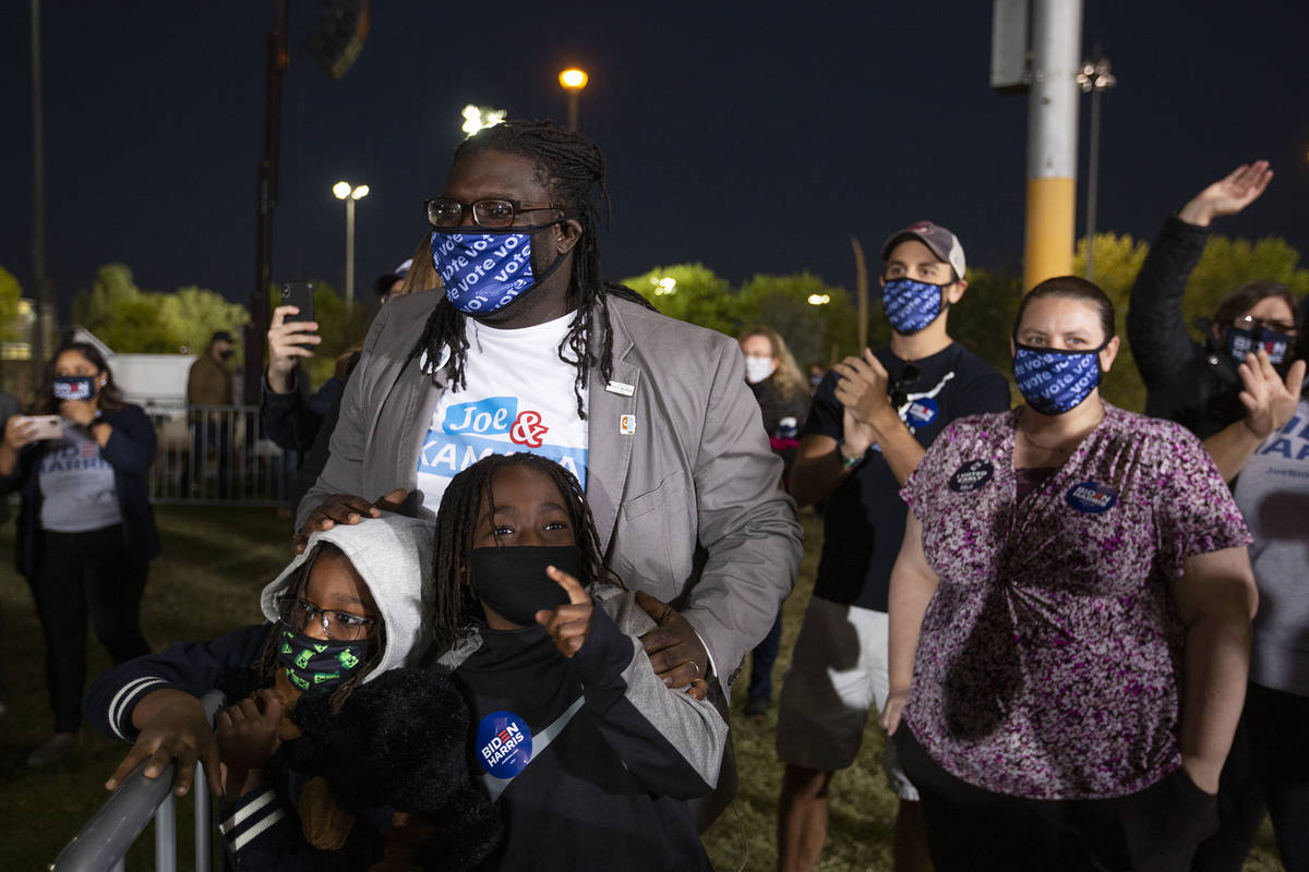 Ethan Austin, 5, left, and Ender Austin, center left, 8, gather to wave as vice presidential ca ...