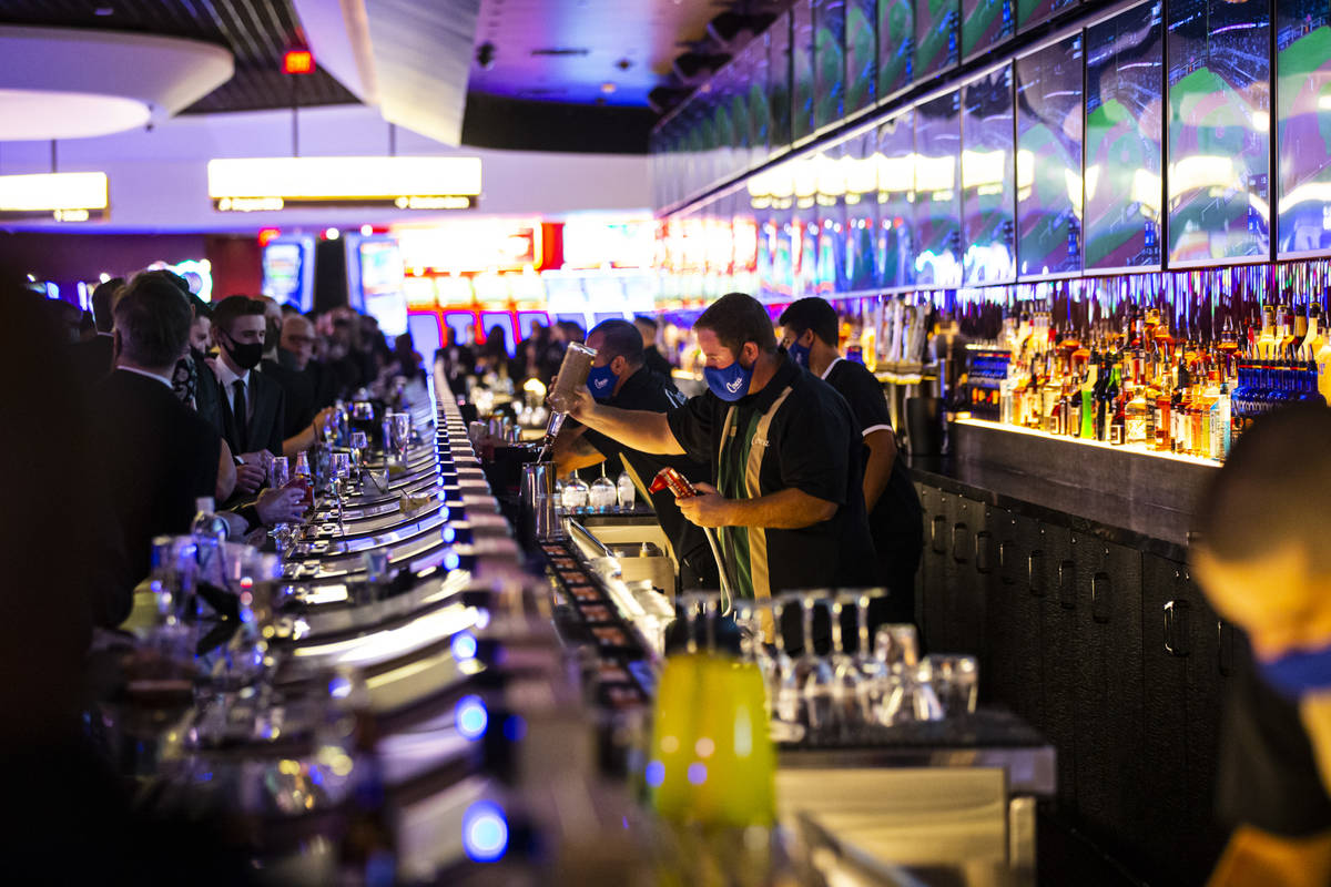 Bartenders prepare drinks at the Mega Bar at Circa during the VIP black-tie grand opening event ...